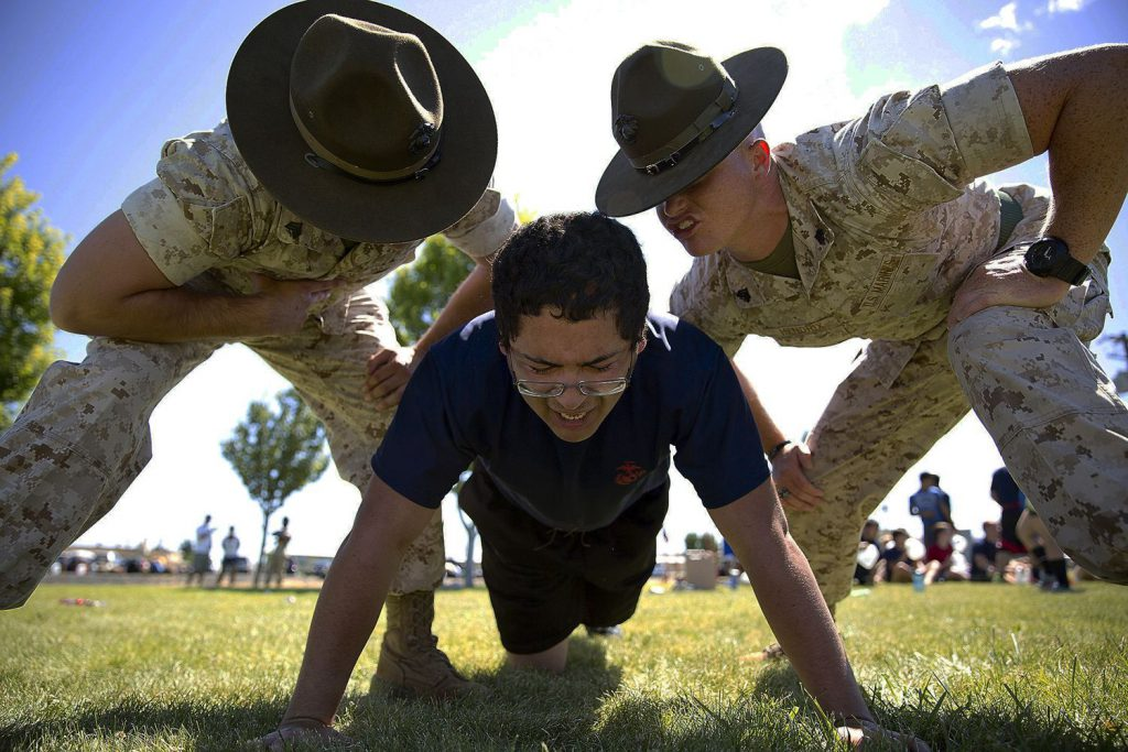 Military officers yelling at a man doing a pushup